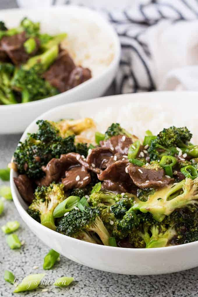 Two bowls of beef and broccoli served with steamed rice.