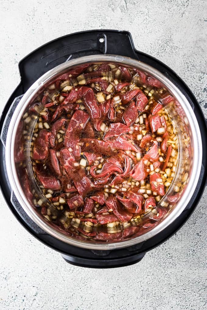 Uncooked beef and sauce in the pressure cooker liner.