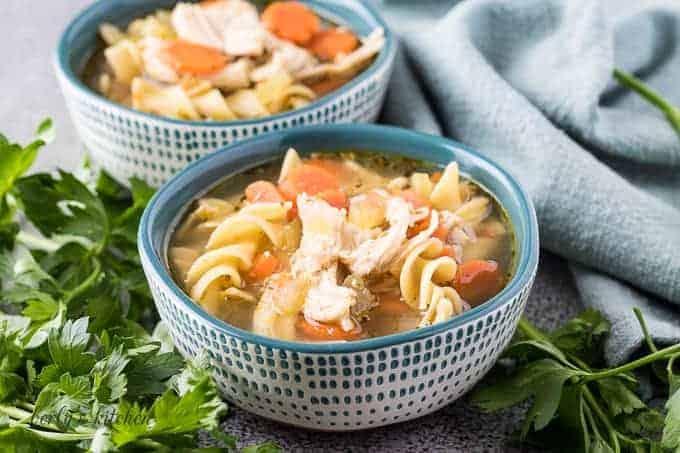 Two decorative bowls of the Instant Pot chicken noodle soup.