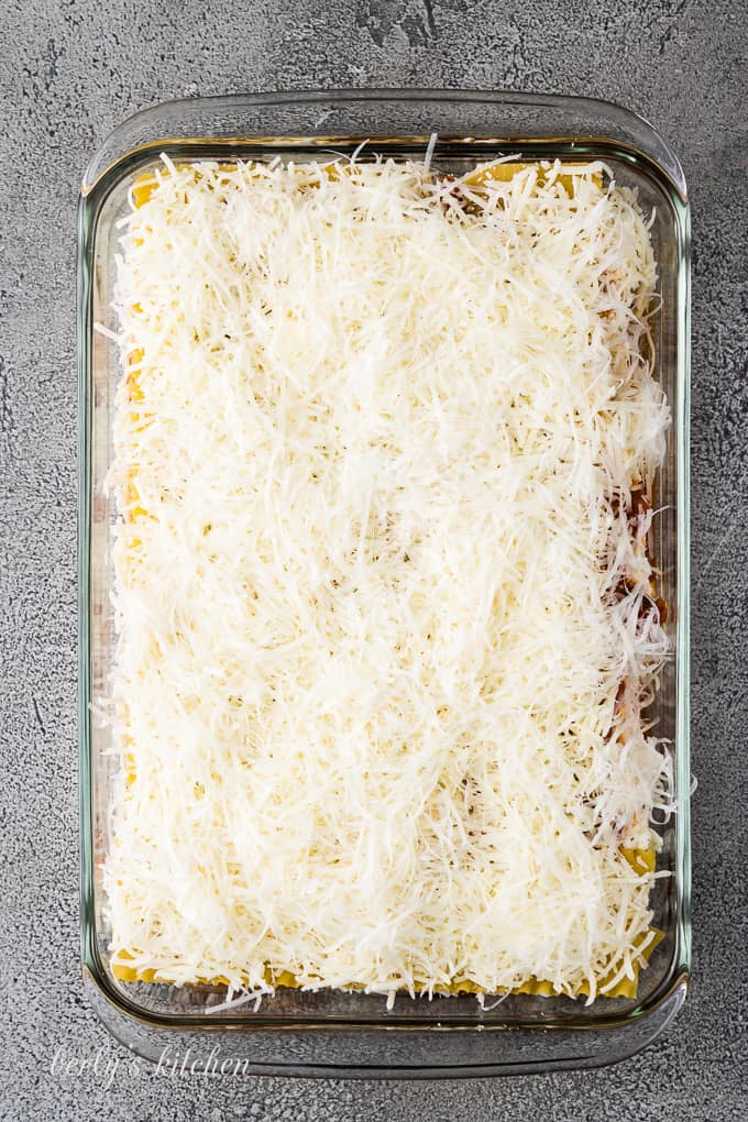 Shredded mozzarella and parmesan cheese top off the unbaked lasagna.