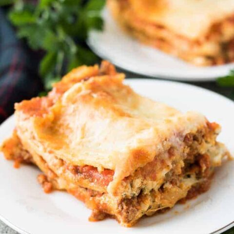 Slices of lasagna on small plates surrounded by fresh parsley.