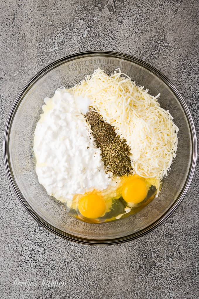 Mozzarella cheese, eggs, and spices in a large mixing bowl.