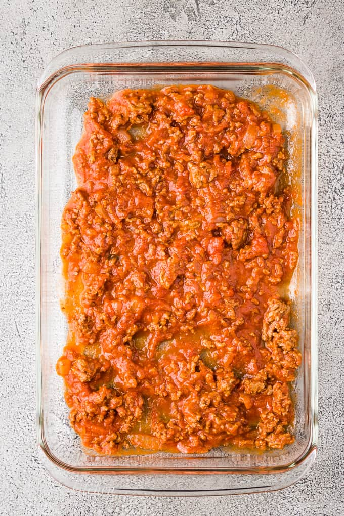 A scoop of even spread marinara in a baking dish.