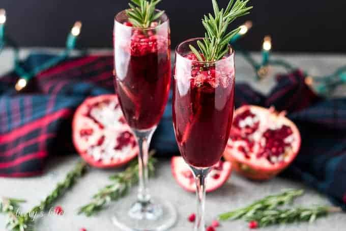Two pomegranate mimosas served in champagne glasses garnished with rosemary.