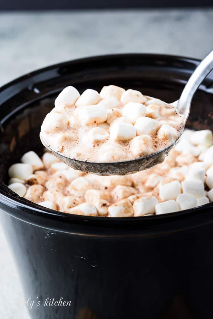 A large ladle of the cocoa topped with melting marshmallows.