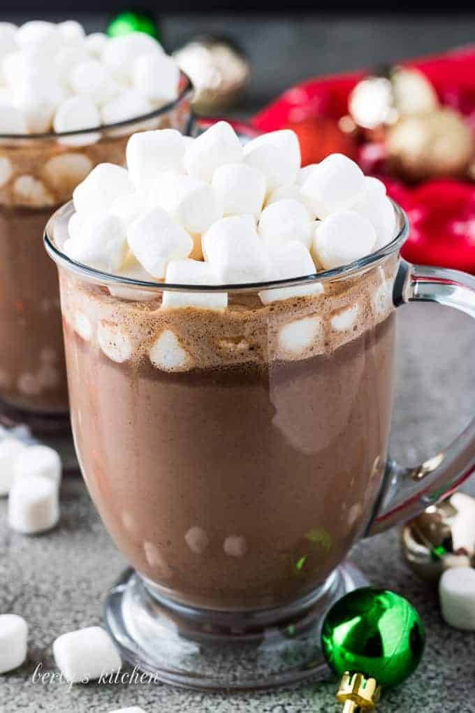 The hot cocoa served in a glass mug with marshmallows.
