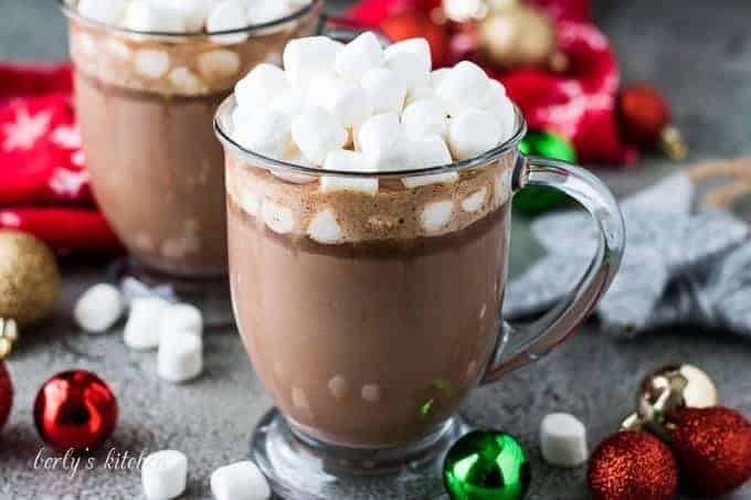 Two mugs of slow cooker hot chocolate topped with marshmallows.