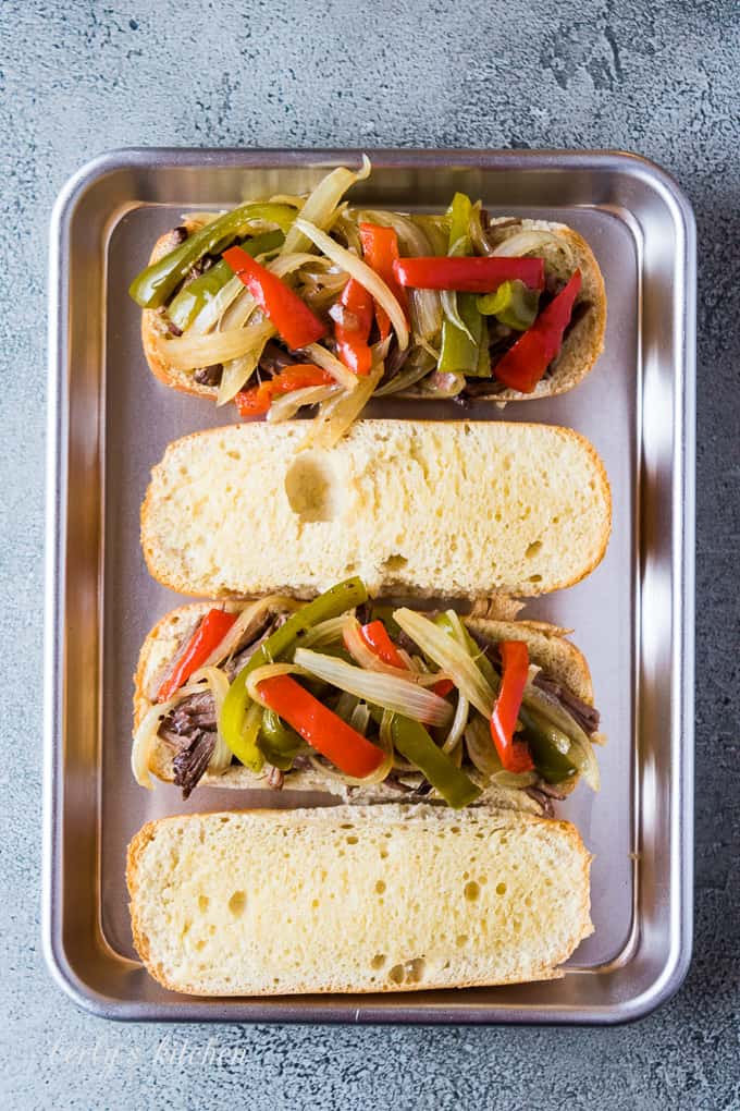 Shredded beef, onions, and peppers on a sliced hoagie bun.