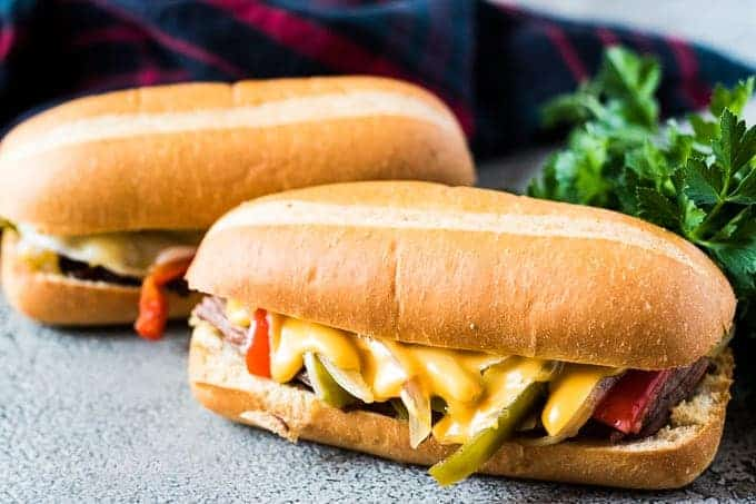 Two philly cheesesteak sandwiches with provolone or cheddar cheese sauce.