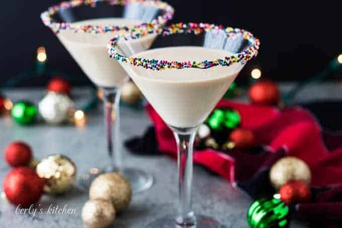Two large sugar cookie martinis garnished with colorful rainbow sprinkles.