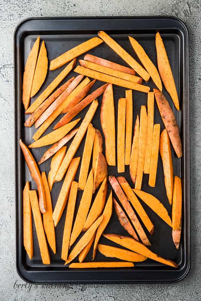 Sweet potato fries on a large sheet pan.
