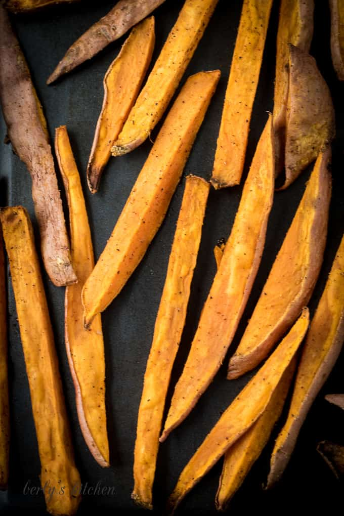 Close up of baked sweet potato fries on a sheet pan.