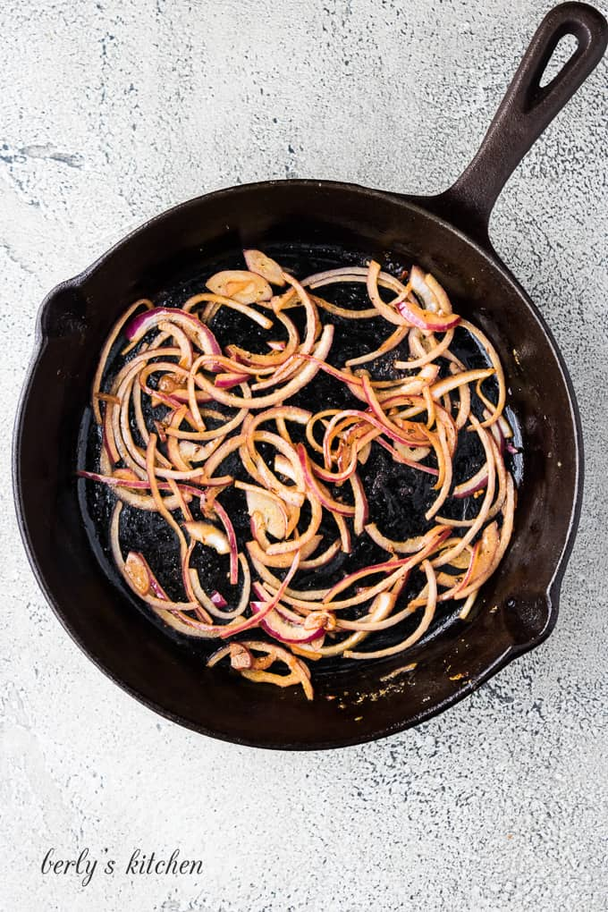 Sliced red onions are sauteing in the cast iron skillet.