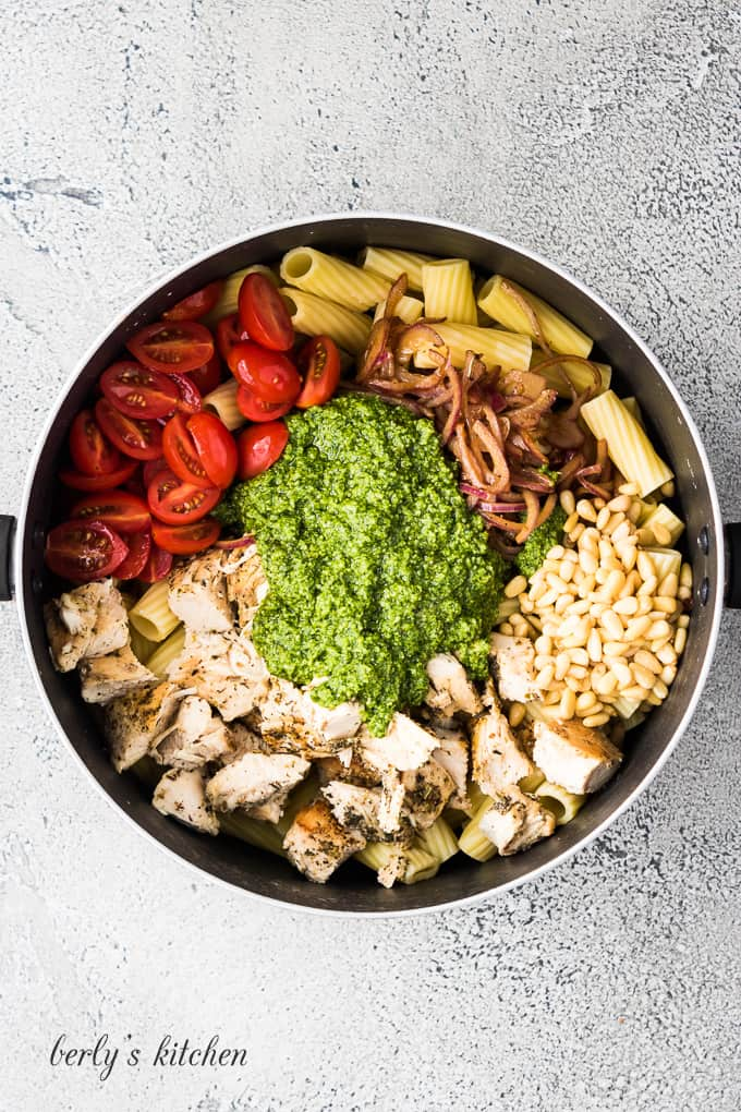 Chicken, pesto sauce and other ingredients in a large pan.