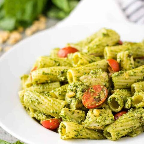 The finished chicken pesto pasta in a large decorative bowl.