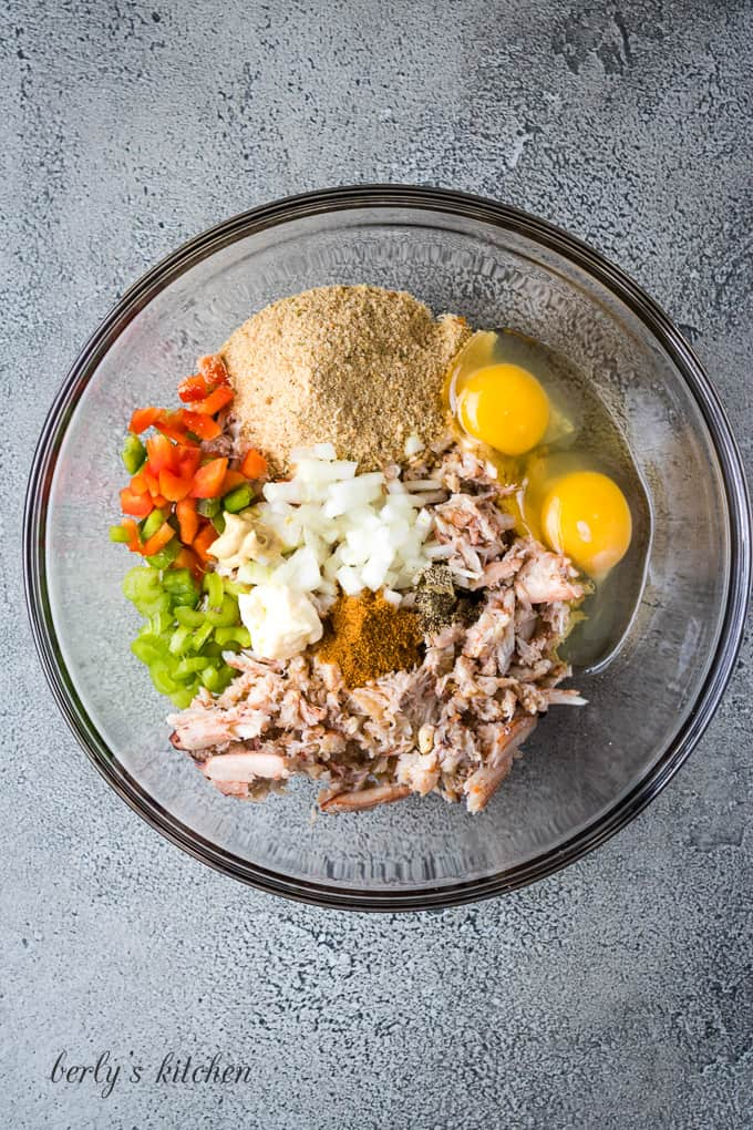 Crab, eggs, and other ingredients in a mixing glass bowl.
