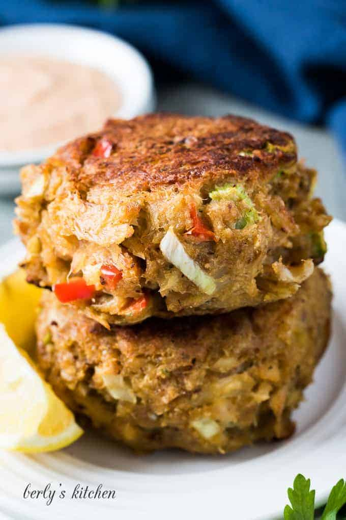 The homemade crab cakes stacked on a small decorative plate.