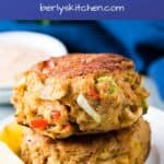 Homemade Crab cakes stacked on a plate with lemon wedges.