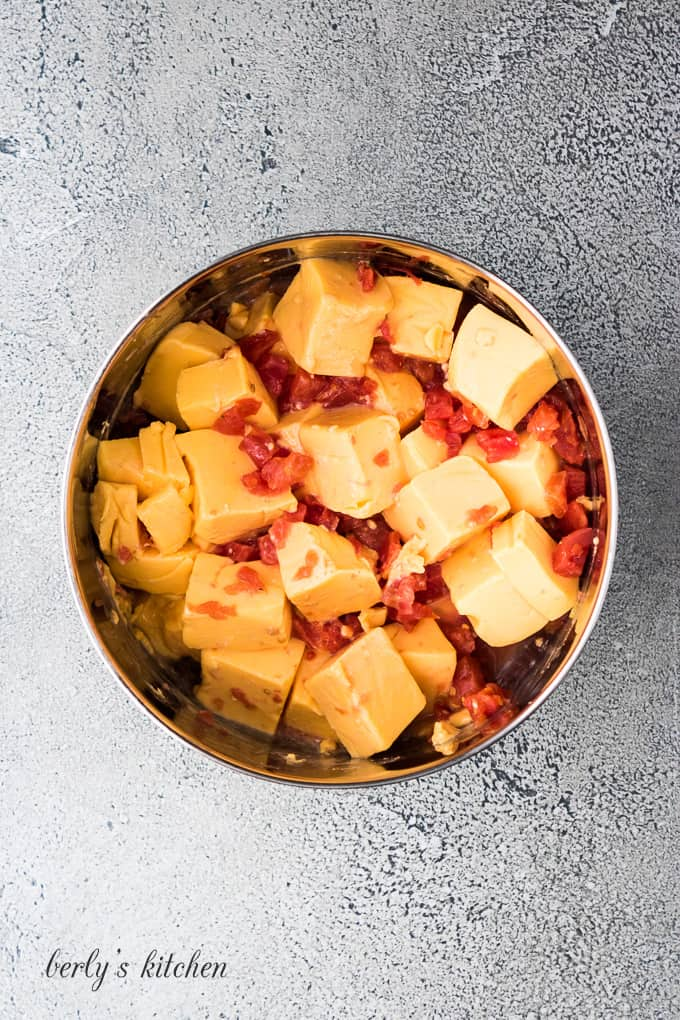 Cubed Velveeta, diced tomatoes and chiles in a metal bowl.