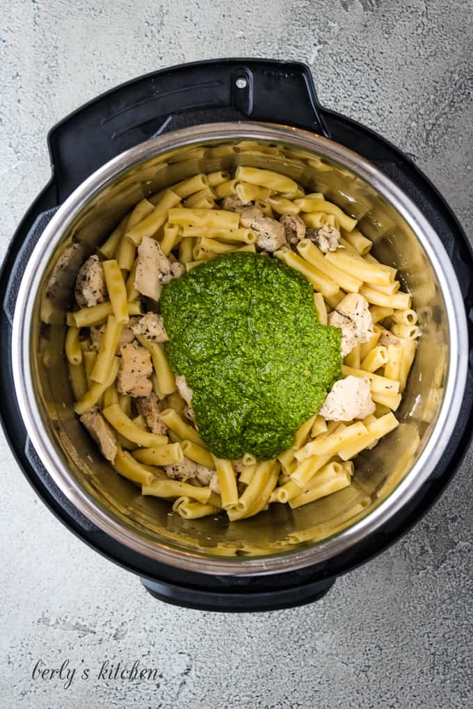 The meat and noodles have cooked and pesto has been added.