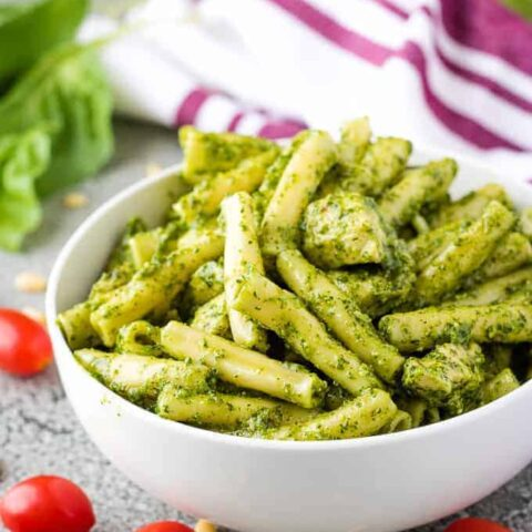 The pesto pasta in a bowl surrounded by cherry tomatoes.