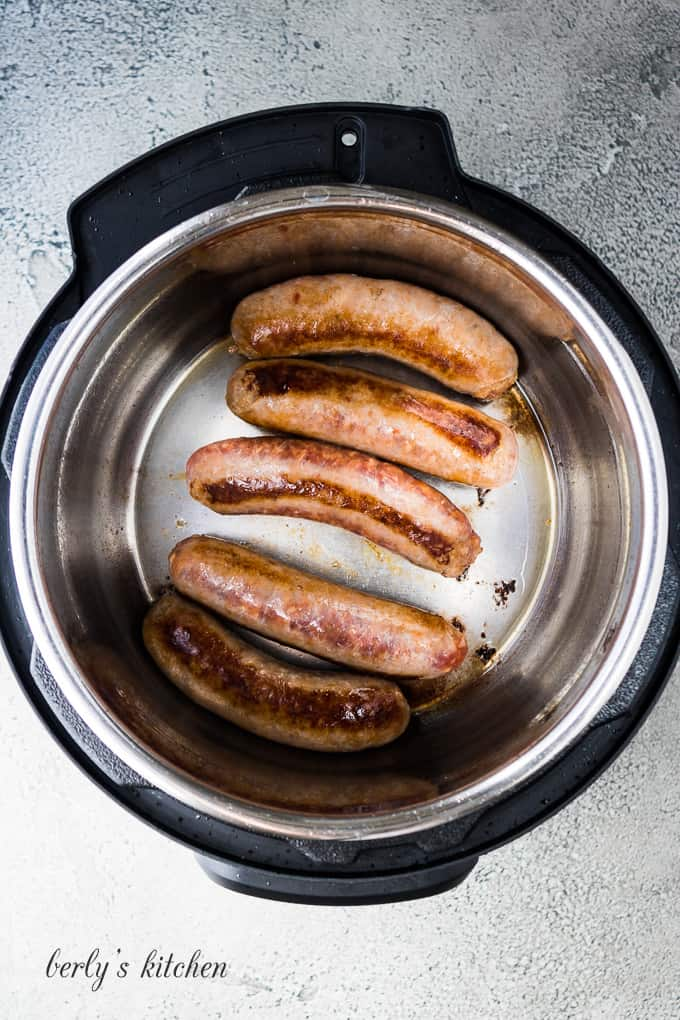 Five Italian sausage links sauteing in the preheated pressure cooker.