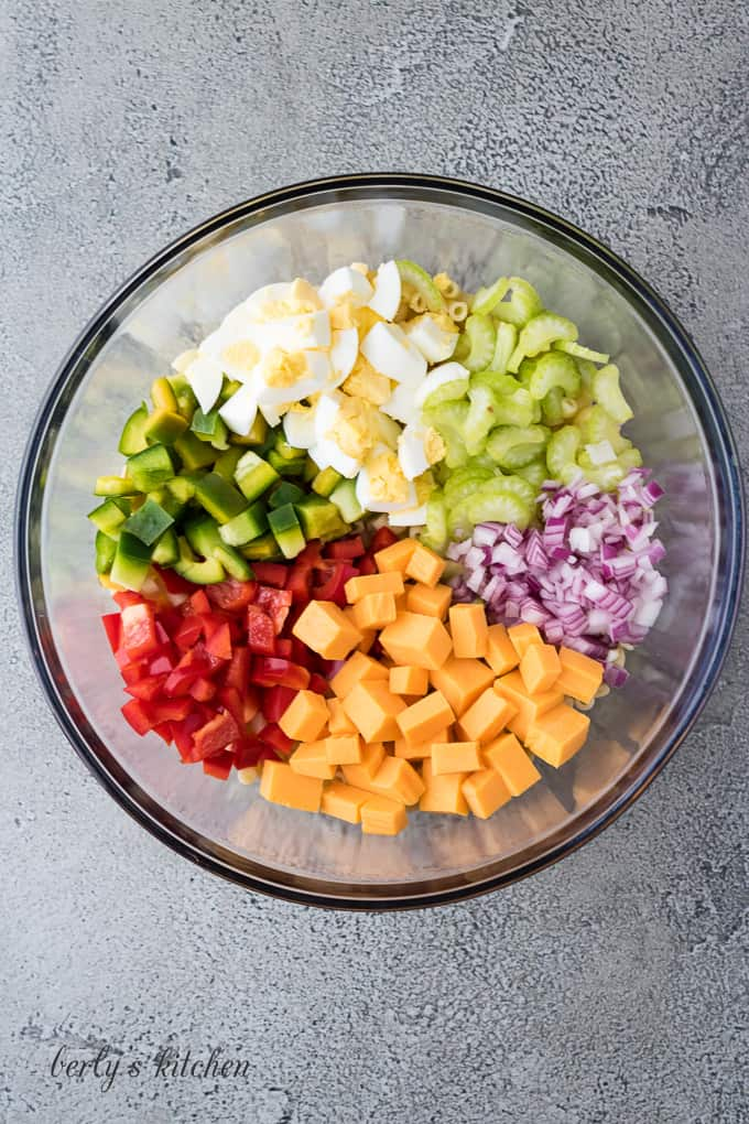 Pasta noodles, diced veggies, and cheese in a mixing bowl.