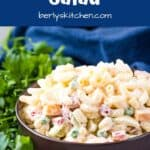 The finished macaroni salad recipe in a decorative brown bowl.