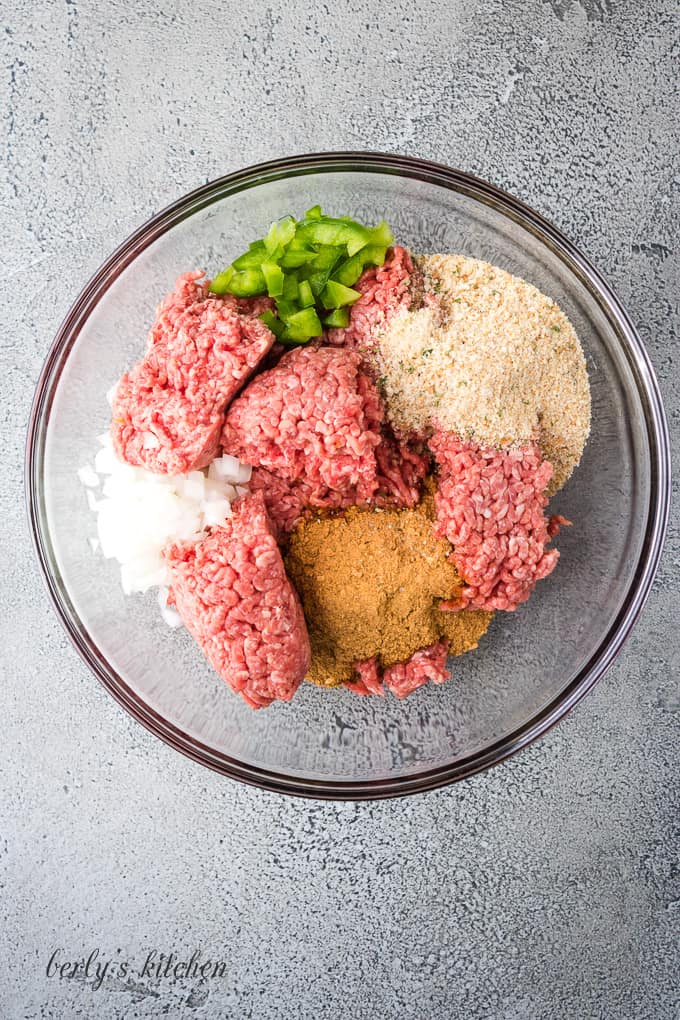 Ground beef and other ingredients in a large mixing bowl.