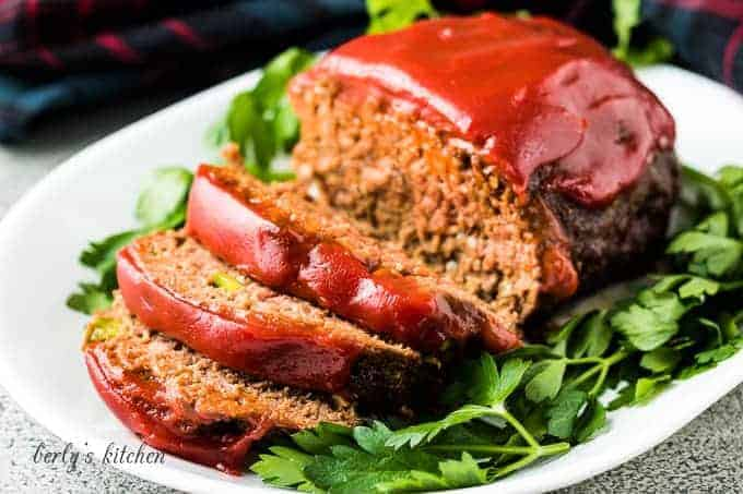 The sliced meatloaf on a platter and topped with ketchup.