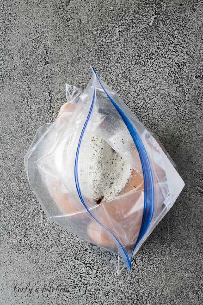 Two chicken breasts in a freezer bag with ranch seasoning.
