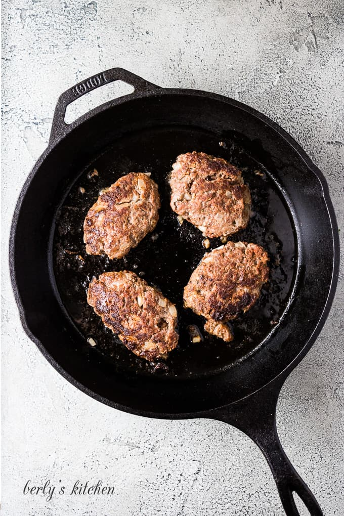 The beef mixture formed into patties cooking in the skillet.