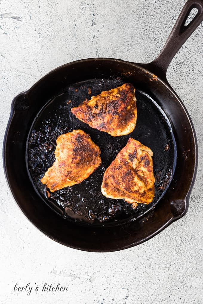 Three seasoned chicken breasts cooking in a cast iron skillet.