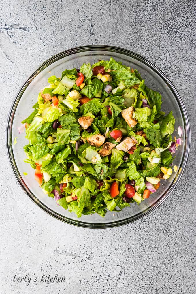 All of the ingredients have been tossed with chopped lettuce.