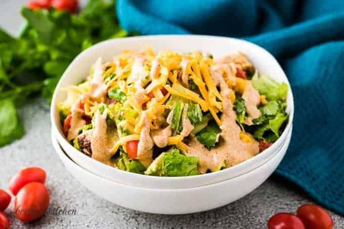 The finished grilled chicken salad topped with Southwest salad dressing.