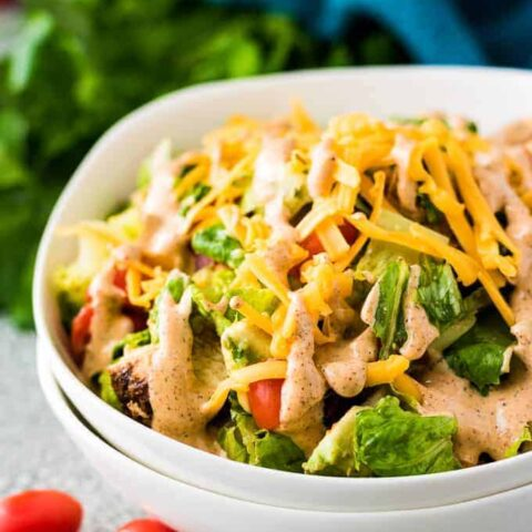 A bowl filled with Southwest chicken salad topped with dressing.