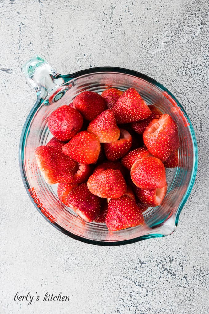 The washed and trimmed strawberries in a glass measuring cup.