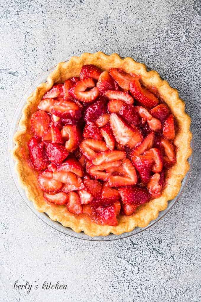 The cooked strawberries have been poured over the fresh berries.