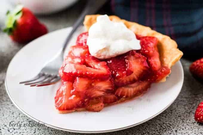 The strawberry pie topped with whipped cream on a plate.
