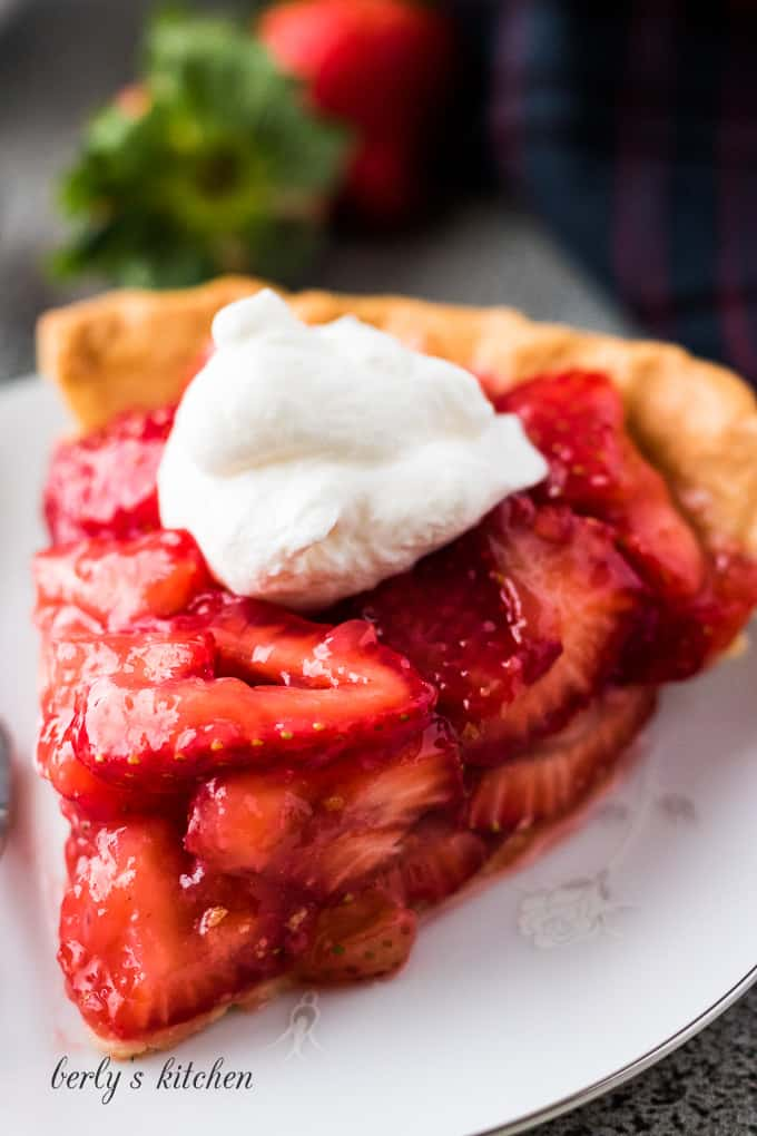 A large slice of pie showing all the fresh strawberries.