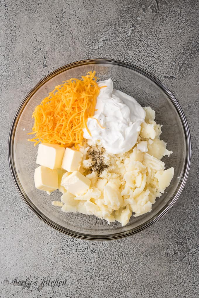 Potatoes, butter, sour cream and cheese in a mixing bowl.