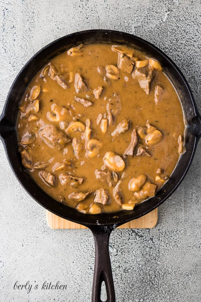 The gravy and meat in a large cast iron skillet.