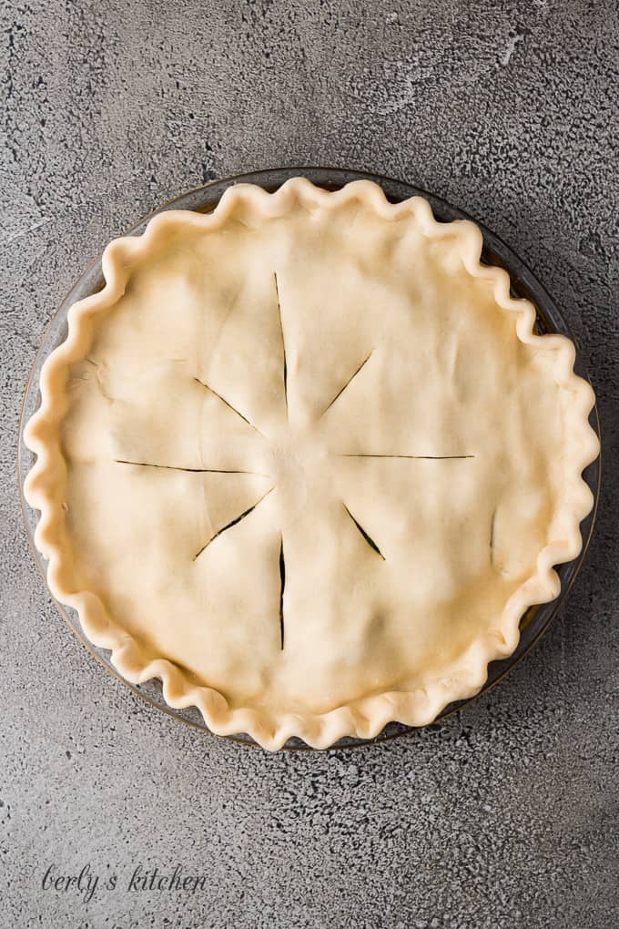 Unbaked pie crust, with vents cut, covering the pie filling.