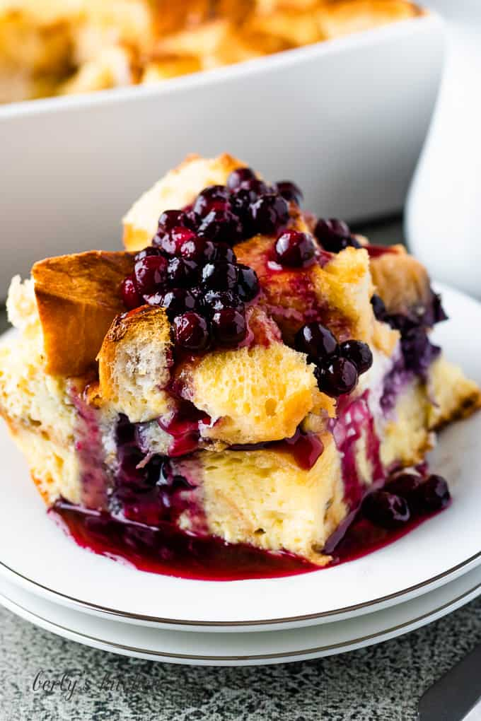 A big piece of French toast casserole topped with blueberry sauce.