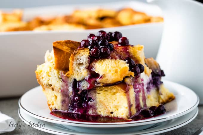A piece of the French toast casserole drizzled with blueberry sauce.