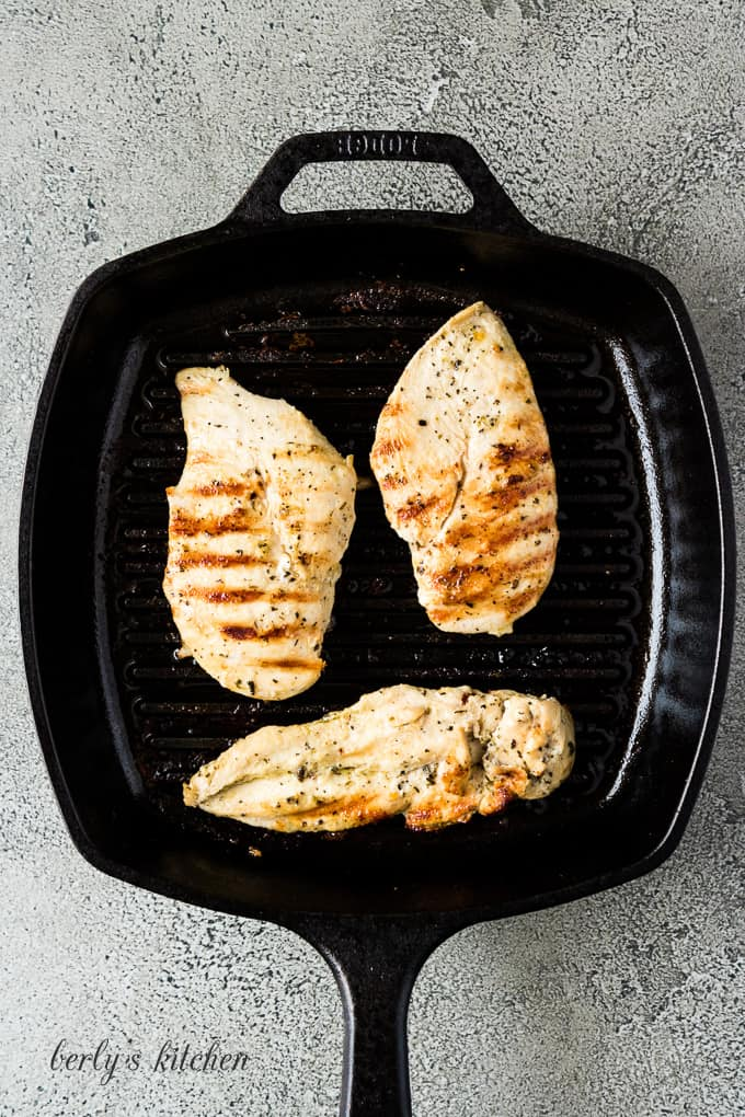Three chicken breasts cooking in a flat iron griddle pan.