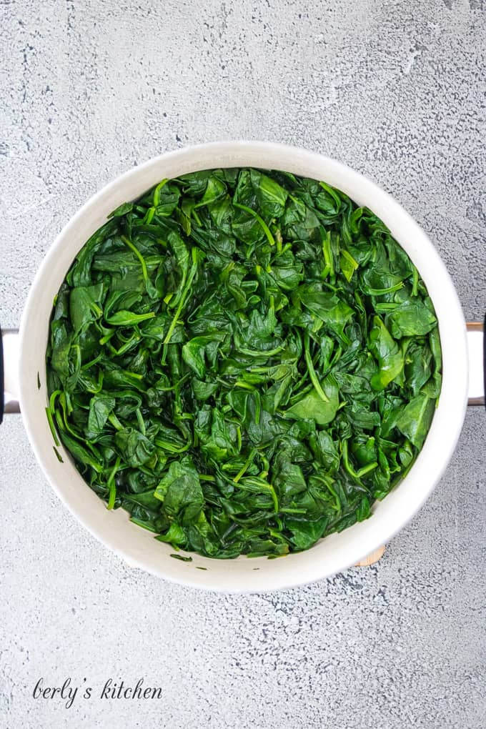 Washed fresh spinach being sauteed in a large metal skillet.