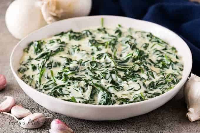 The creamed spinach in a bowl surrounded by garlic cloves.