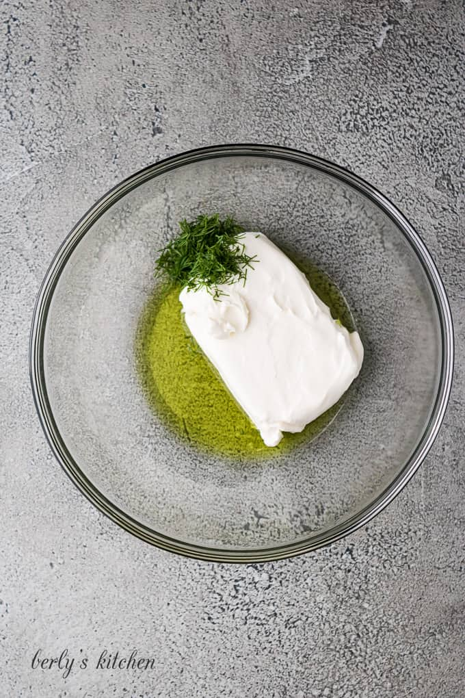 Cream cheese, pickle juice, and fresh dill in a bowl.