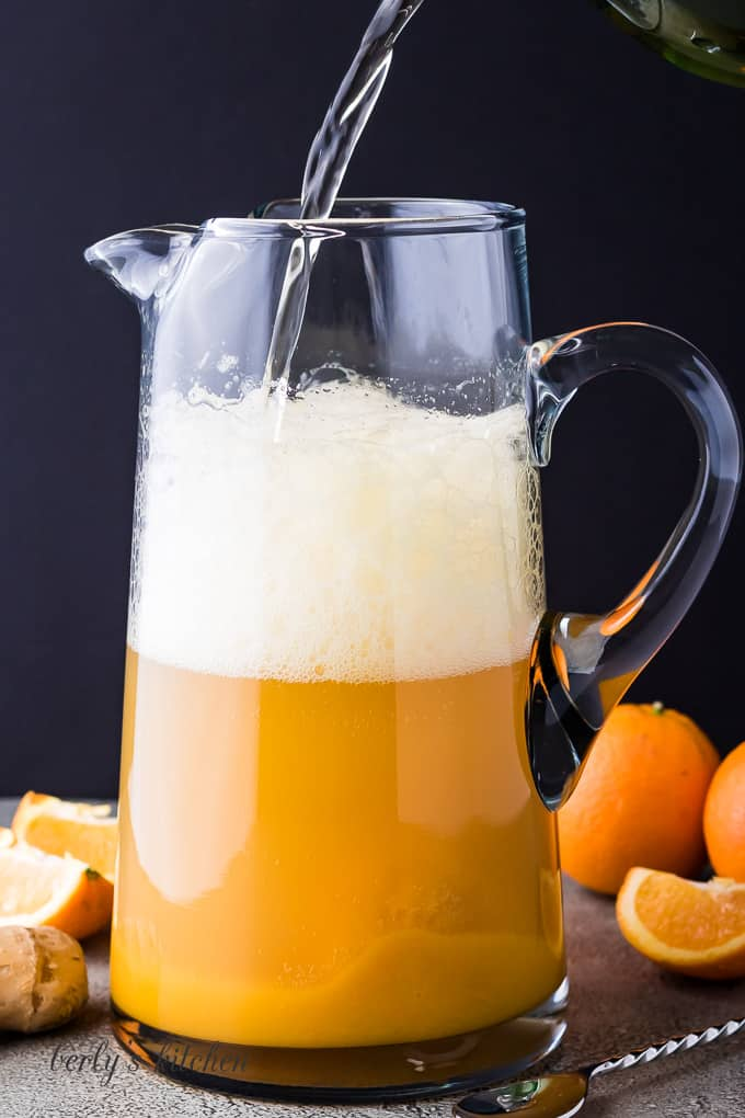 The ginger soda being added to the orange juice concentrate.